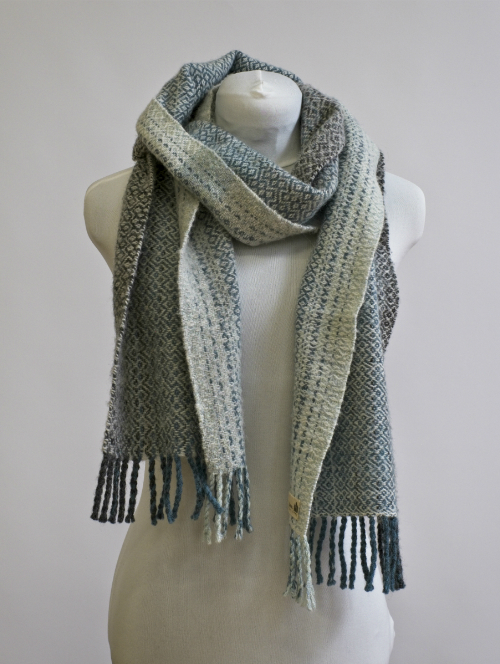 A hand woven brushed Shetland lambswool scarf in a fibinacci gradient of soft greens and blues in a wall of troy draft.