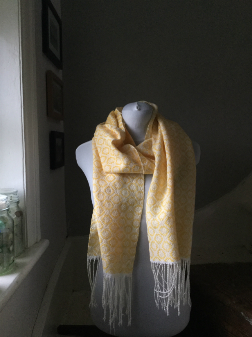 a handwoven scarf in a daisy overshot pattern in yellow merino and natural cotton.