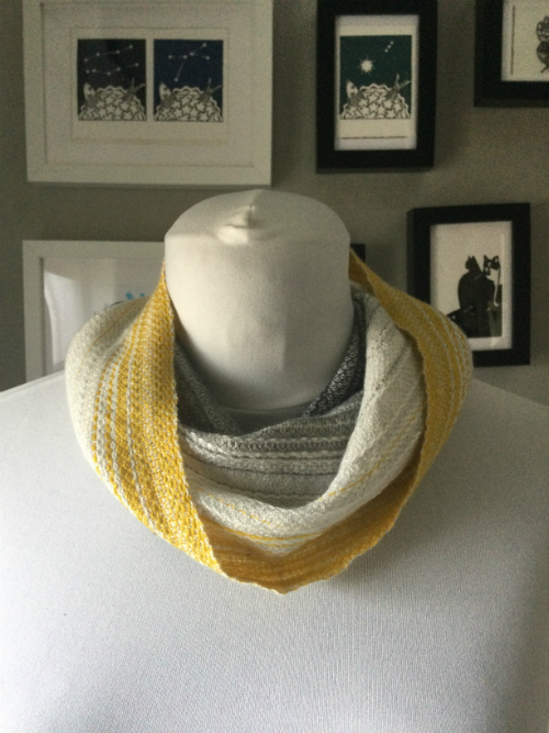 a handwoven cowl in shades of grey and yellow on a mannequin