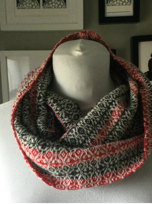 Snowflake merino cowl in red, charcoal and silver on a mannequin.