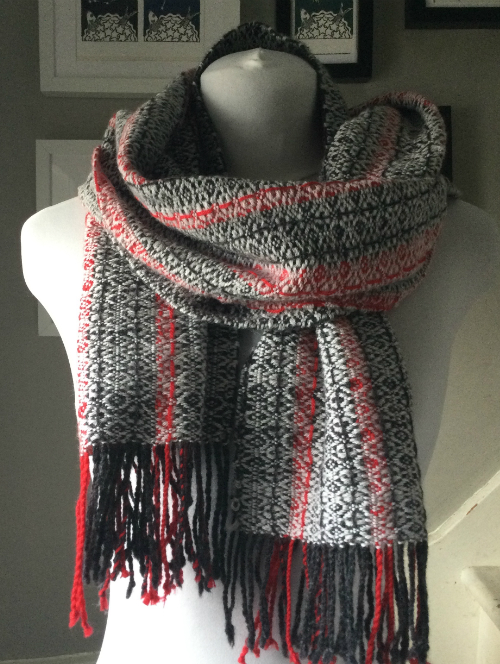 A handwoven scarf in a snowflake draft in red, charcoal and silver on a mannequin.